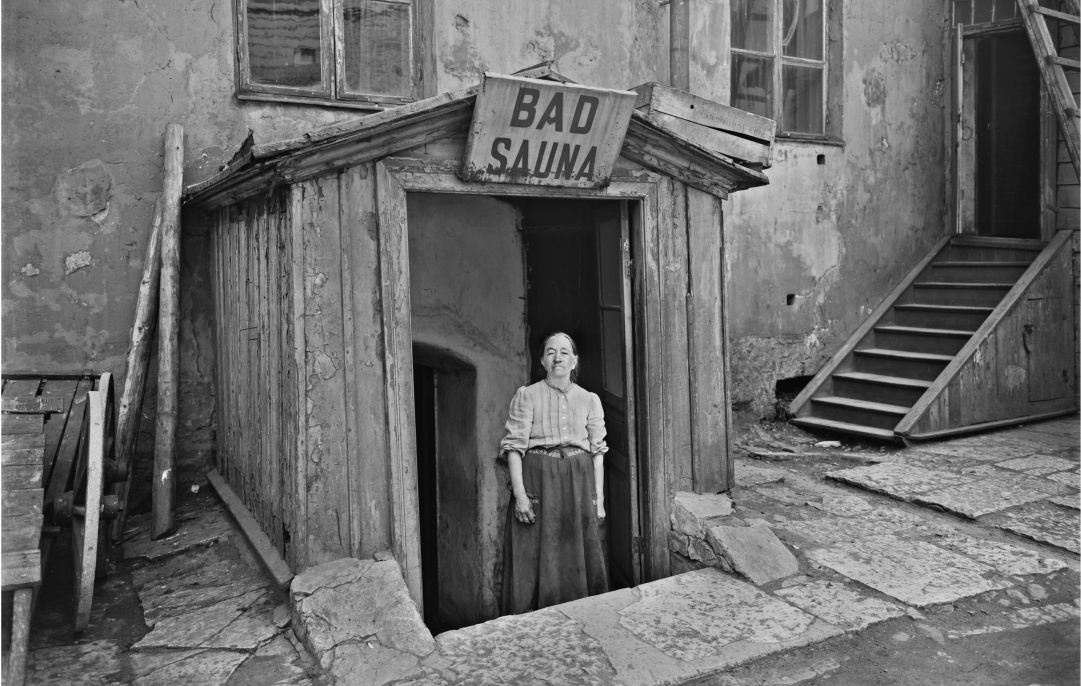 A photo in black and white of a person standing in the doorway of a sauna.