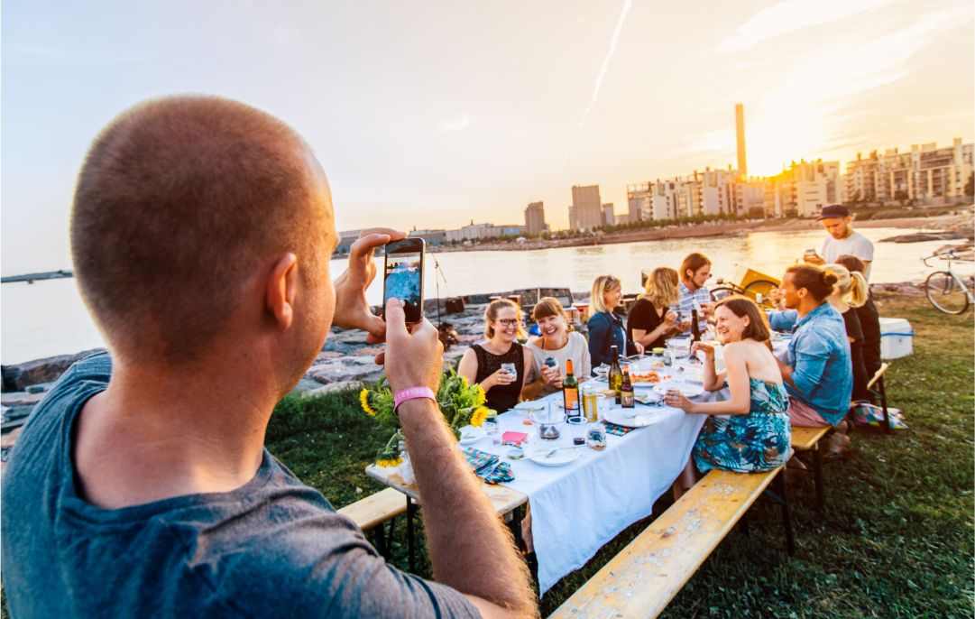 A person taking a photo of people sitting at an outdoor table.