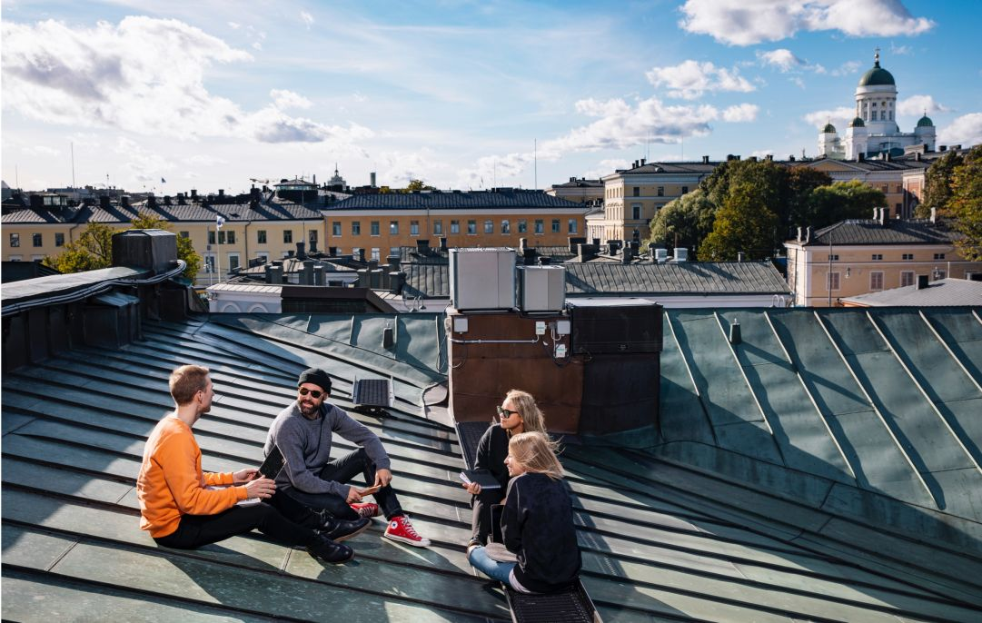 Four people sitting on a roof in the city.