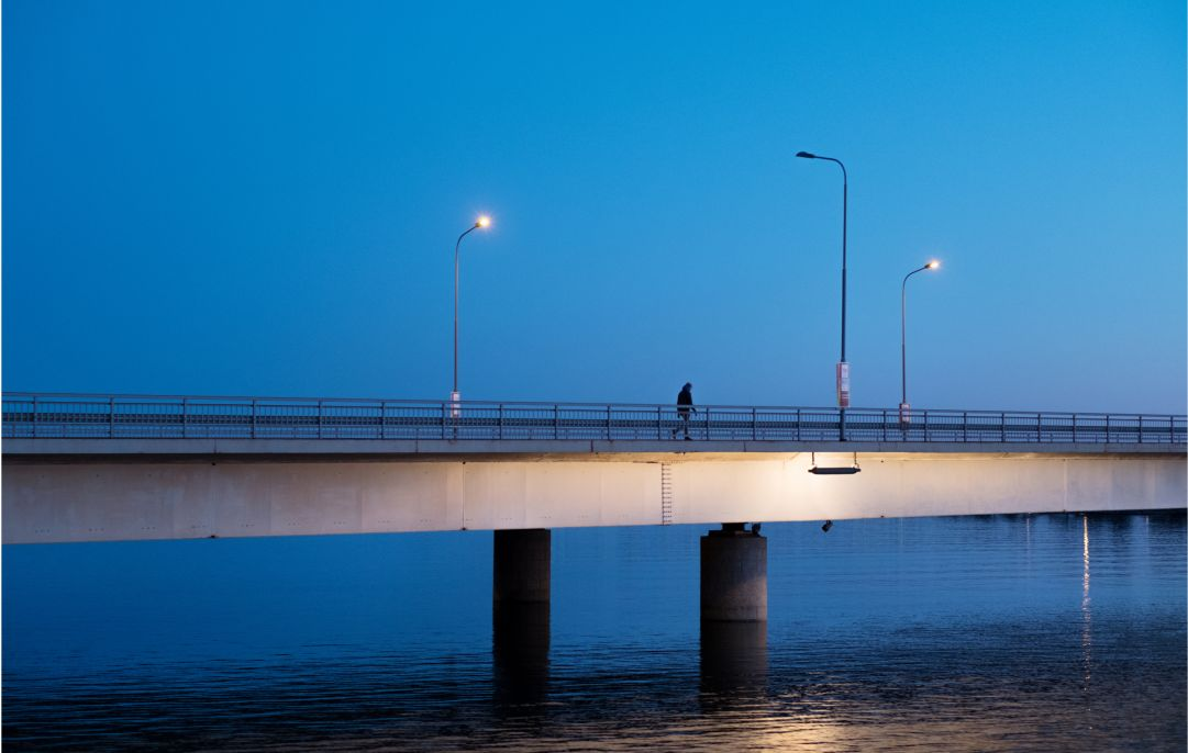 A solitary person walking over a bridge.