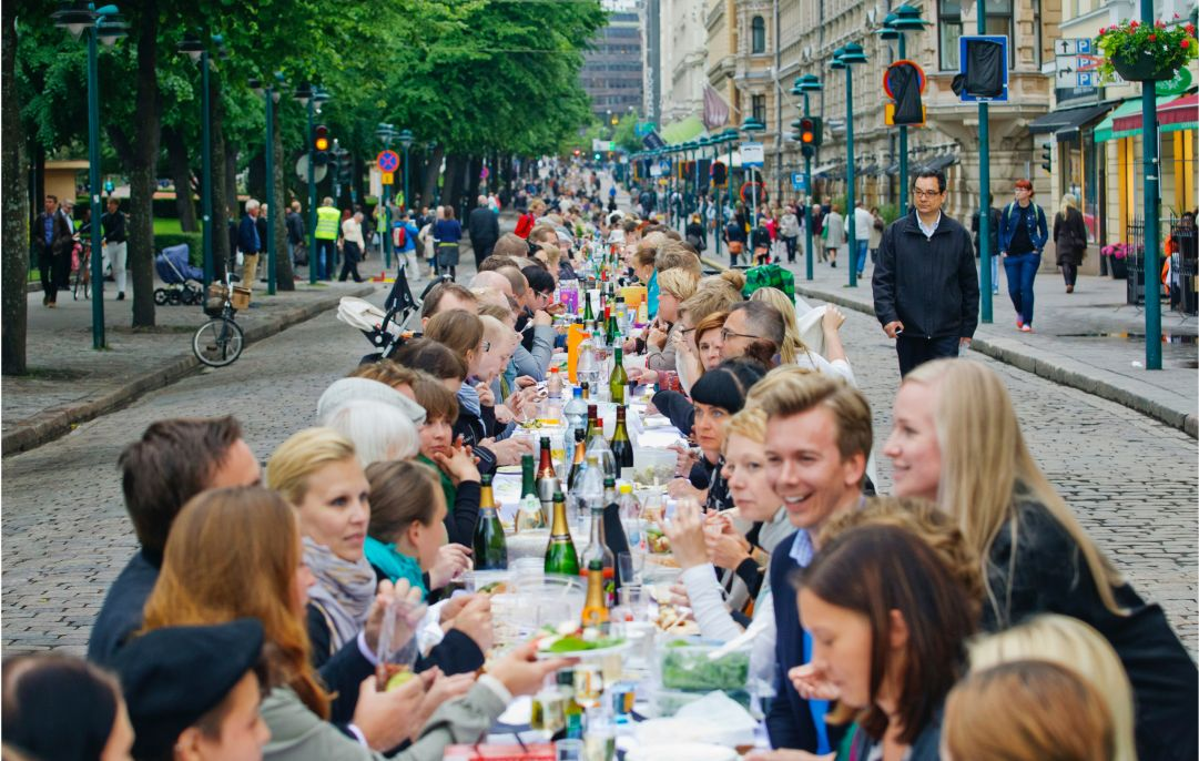 A long line of dining tables in the middle of the street filled with foods.